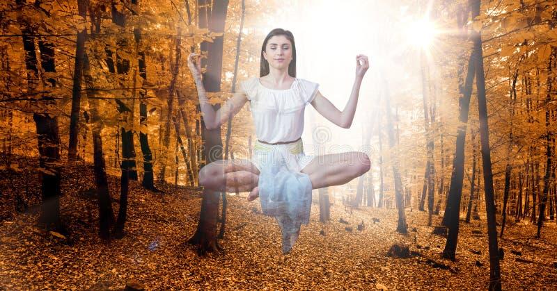 Dubbel exponering av kvinnan som mediterar i midair på höstskogen arkivbild