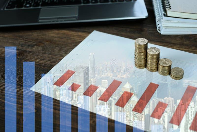 Dubbel exponering av mynt staplar med anteckningsbokbärbar datordatoren och den finansiella grafen på vitbok på arbetetabellen, a arkivfoton
