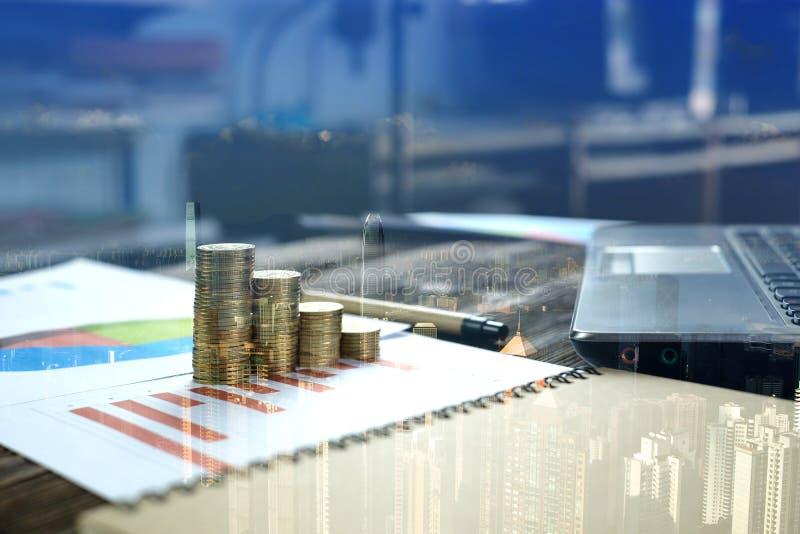 Dubbel exponering av mynt staplar med anteckningsbokdatoren och den finansiella grafen på vitbok, stadsbakgrund, affärsplanläggni arkivfoton