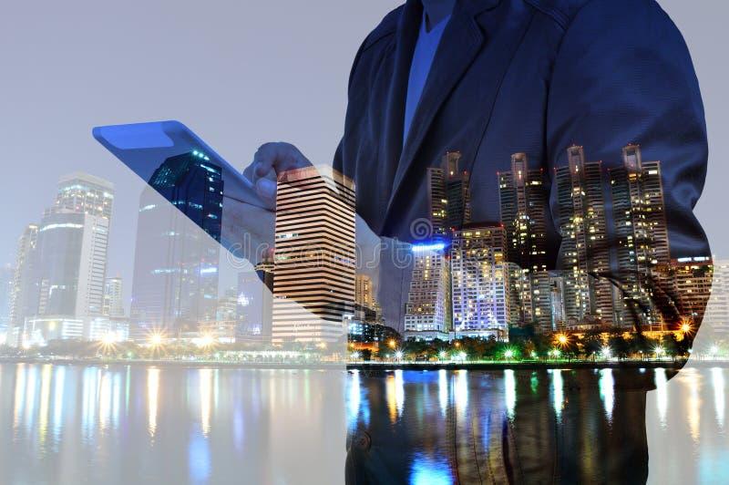 Dubbel exponering av staden och affärsmannen som använder den digitala minnestavlan arkivbild