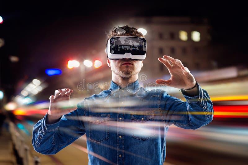 Dubbel exponering, bärande virtuell verklighet för man rullar med ögonen, nattstaden