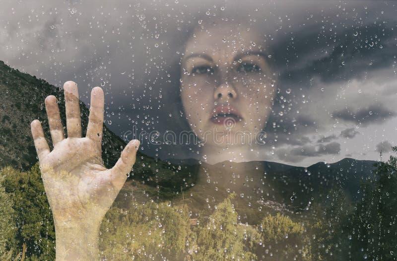 Dubbel exponering en kvinnlig bak fönstret fotografering för bildbyråer