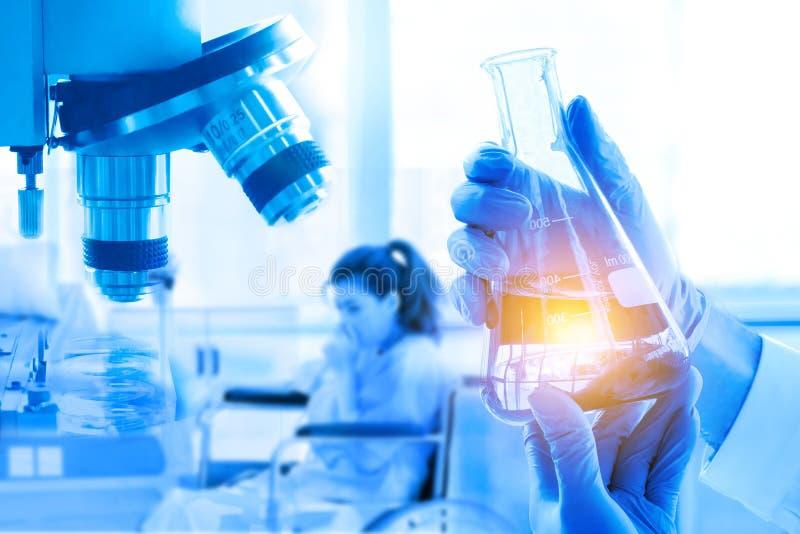 Dubbel exponering, handinnehavflaska, mikroskop, i medicinsk forskning på laboratoriumet royaltyfria bilder