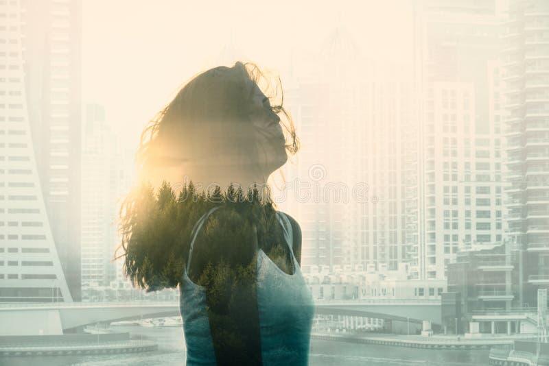 Dubbel exponering med den unga kvinnan i den moderna cityscapen och skogen royaltyfria bilder