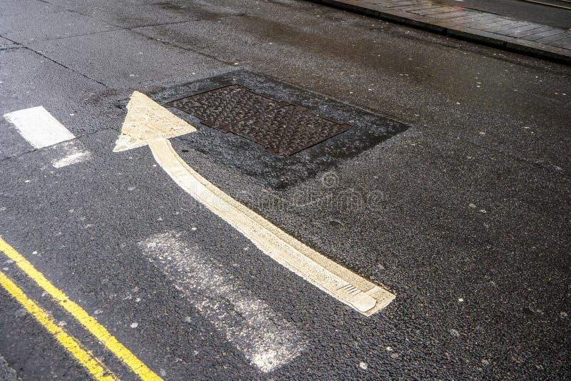 Dubbel gul linje och pil som pekar litet högert på våt asfalt royaltyfri bild