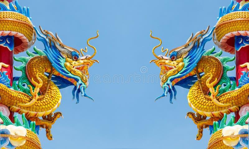 Dubbel guld- drakestaty på bakgrund för blå himmel royaltyfri bild