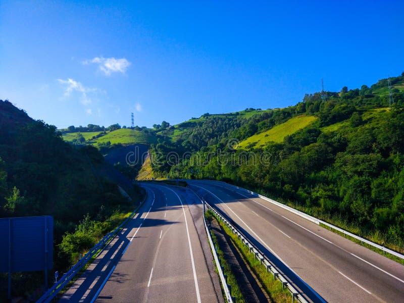 Dubbel huvudväg som korsar ett grönt berg i Asturias, Spanien royaltyfri fotografi