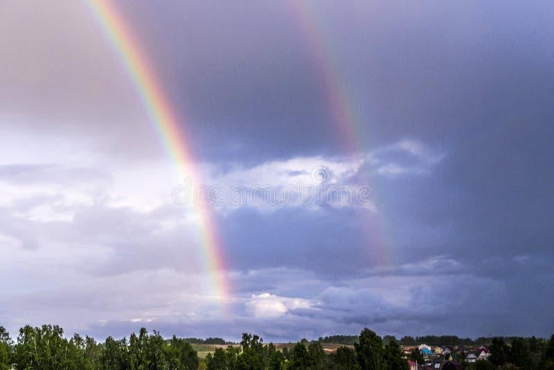 Dubbel regnbåge över skogen och husen fotografering för bildbyråer