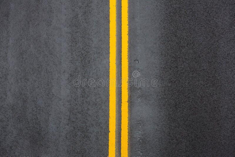 Dubbel spärrlinje för guling på asfalt royaltyfria foton