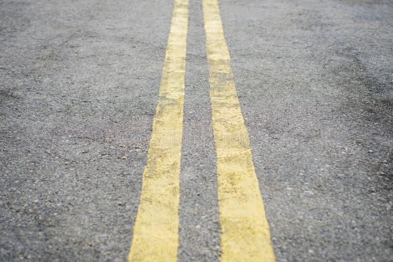 Dubbel sp?rrlinje f?r guling Vägteckning på asfalt på gatan Huvudvägyttersida med dubbla gula linjer royaltyfria foton