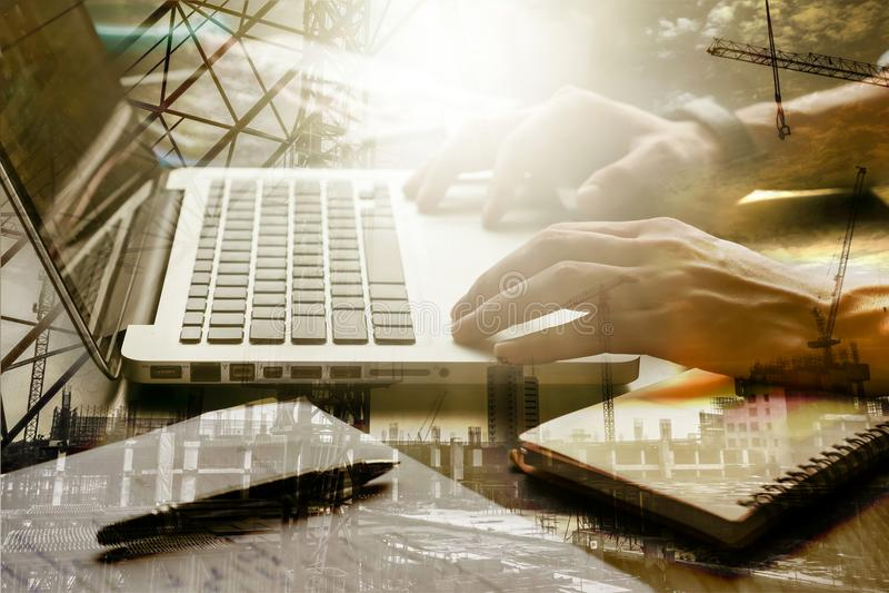 Dubbel van mannelijke handen wordt blootgesteld die aan laptop met het gebouw werken dat stock foto