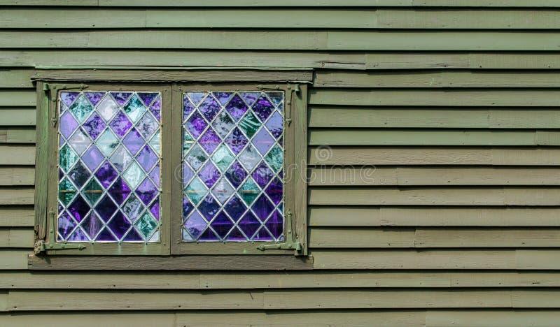 Dubbel venster met purpere ruiten in een diamantpatroon in de muur van een koloniaal gebouw royalty-vrije stock fotografie