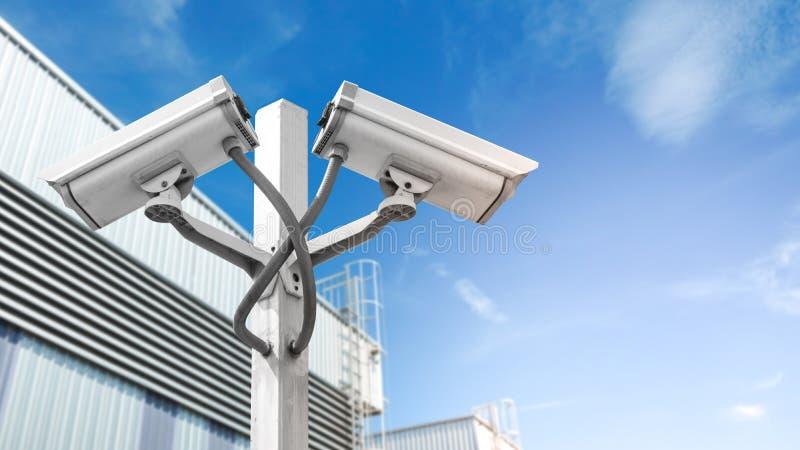 Dubbelbevakningcctv-kameran på pol i fabriken som är industriell med signalljusljuseffekt och copyspace, använder för bevakningka royaltyfria foton