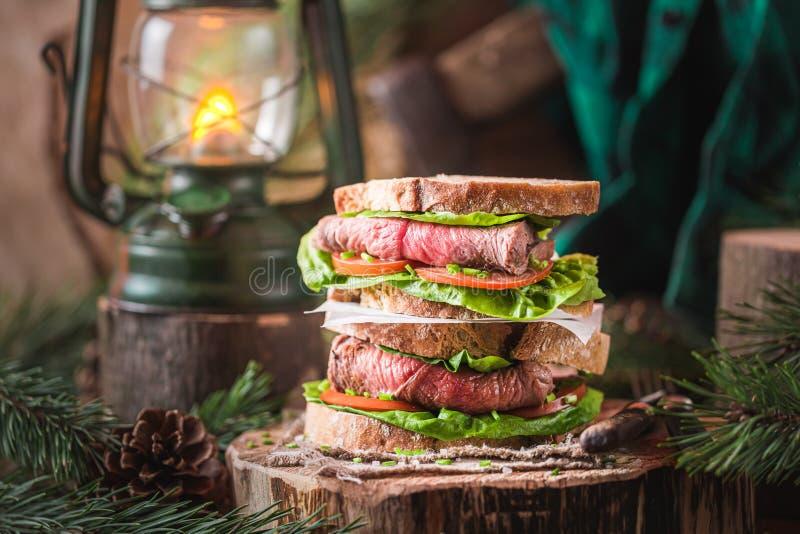 Dubbeldekerboterham met rundvlees, tomaten en sla stock afbeelding
