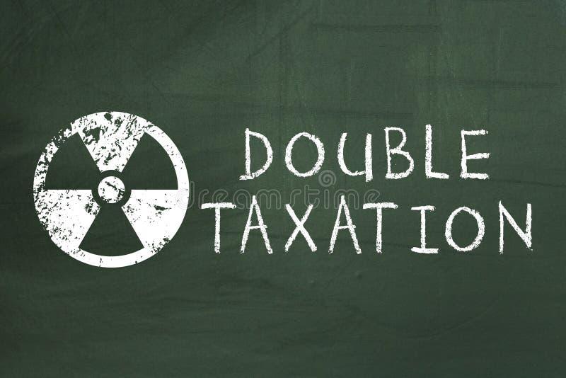 Dubbele belastingheffingsgevaar, financiën, bankwezen, boekhoudingsconcept op groen bord royalty-vrije stock foto's