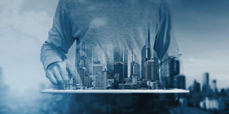 Dubbele blootstelling, een mens digitale tablet gebruiken, en modern gebouwenhologram die Onroerende goederenzaken en bouwtechnol stock fotografie
