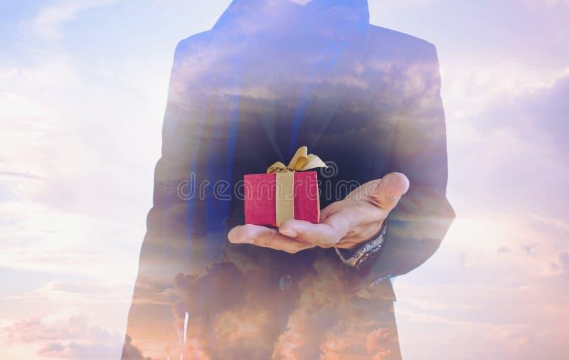 Dubbele blootstelling, uitstekende toon, zakenman met giftdoos op hand, en mooie fantasiehemel stock fotografie