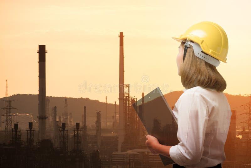 Dubbele blootstelling van bedrijfsvrouw met de achtergrond van de olieraffinaderij stock afbeelding