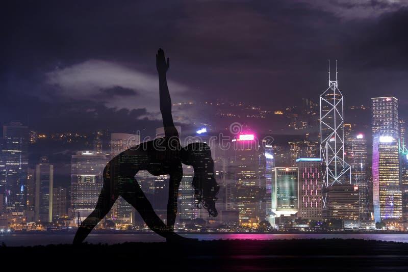 Dubbele blootstelling van de vrouw van de Silhouetyoga tegen Hong Kong-stad stock foto's