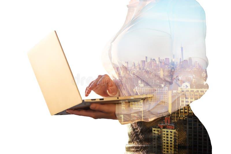 Dubbele blootstelling van een vrouw in het bureaukostuum met laptop en de de stadsachtergrond van New York stock afbeeldingen