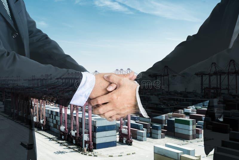 Dubbele Blootstelling van een zakenmanhanddruk op haven met containe stock afbeelding