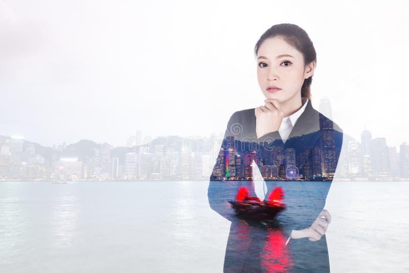 Dubbele blootstelling van het bedrijfsvrouw denken met Hong Kong-stad royalty-vrije stock fotografie