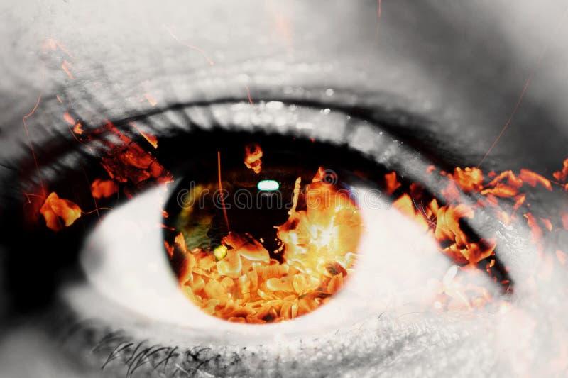 Dubbele blootstelling van het close-up vrouwelijke oog en de hete rode steenkolen van brandhout stock fotografie