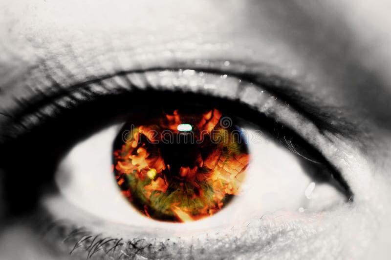 Dubbele blootstelling van het close-up vrouwelijke oog en de hete rode steenkolen van brandhout stock foto's