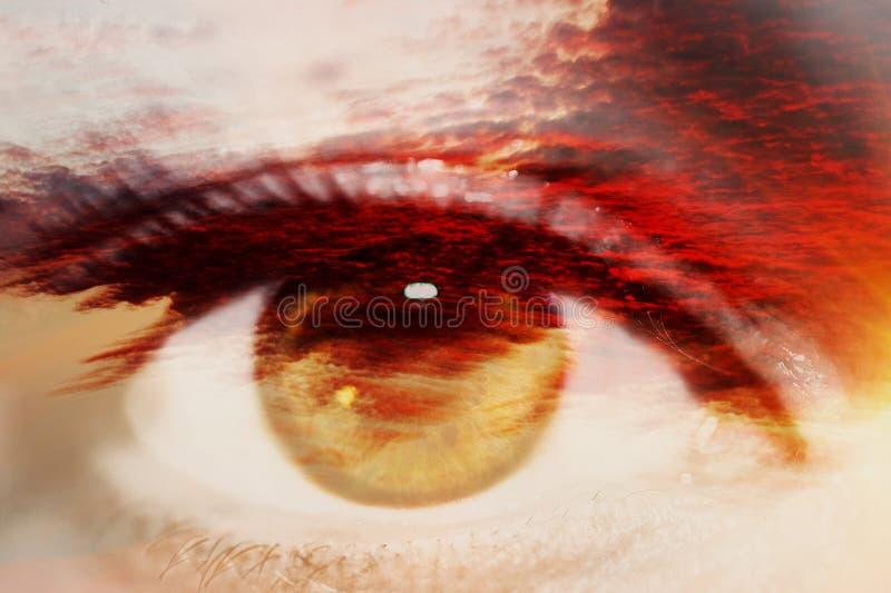 Dubbele blootstelling van het oog van de close-upvrouw en de zonsonderganghemel royalty-vrije stock fotografie