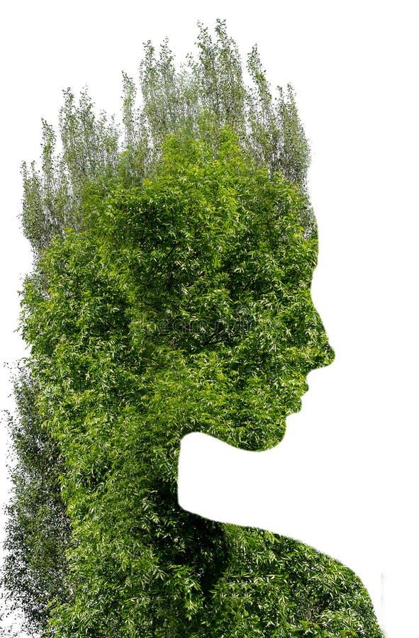 Dubbele blootstelling van jong mooi meisje onder de bladeren en de bomen Portret van aantrekkelijke die dame met foto van boom wo stock foto