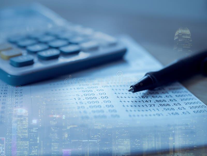 Dubbele blootstelling van stad en het Boek van de Besparingsrekening van Bank voor Bedrijfsfinanciën met pen en calculator royalty-vrije stock afbeeldingen