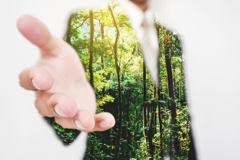 Dubbele blootstelling, Zakenman uitrekkende hand aan hand schok met Groene bomen in de bos vriendschappelijke en duurzame zaken v stock afbeelding