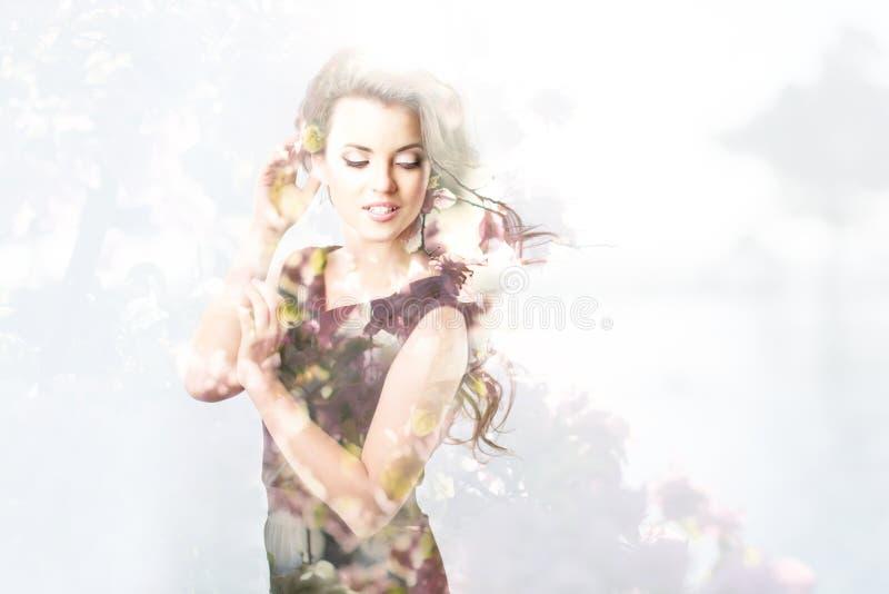 Dubbele blootstellingsaard Portret van mooie jonge vrouw, boom en bloemen royalty-vrije stock afbeelding