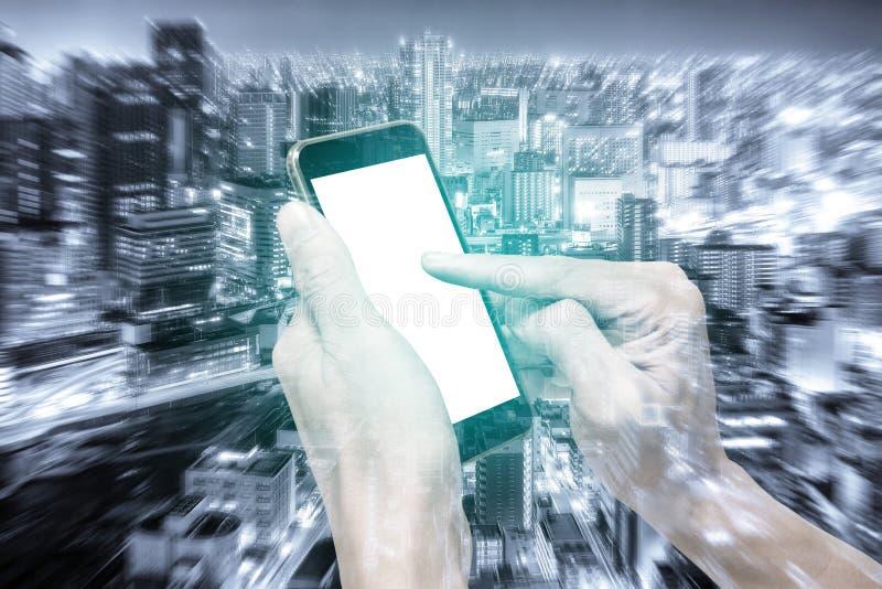 Dubbele blootstellingshanden die smartphone en stad gebruiken stock afbeeldingen