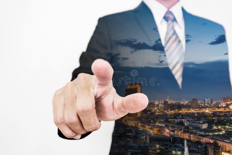 Dubbele blootstellingszakenman die vinger richten aan het scherm met wolkenkrabbercityscape stock afbeelding