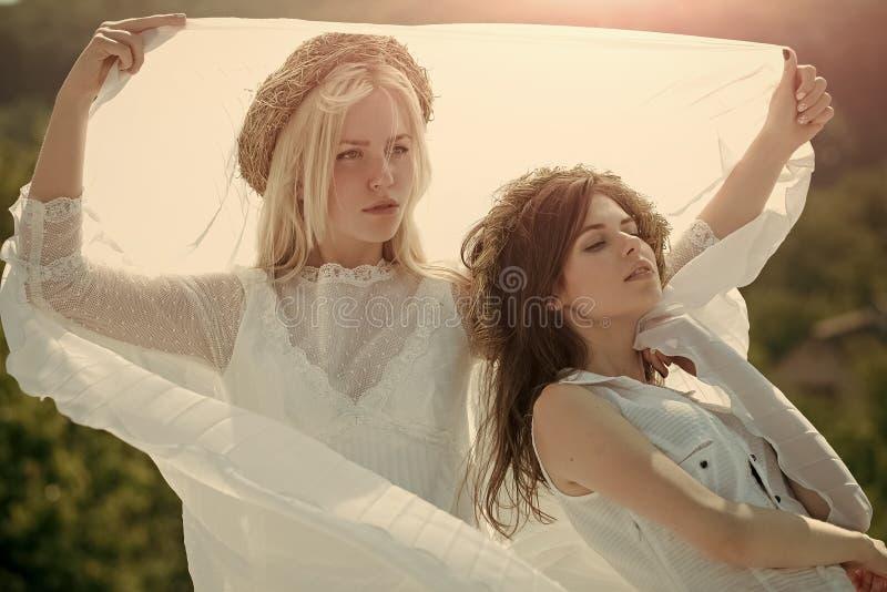 Dubbele bruids reeks op witte rozen Vrouwen met strokronen op blond en donkerbruin haar royalty-vrije stock foto