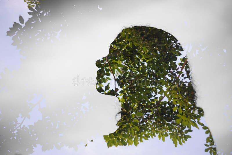 Dubbele exposer van Aziatisch meisje met boomachtergrond stock fotografie