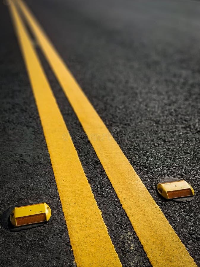 Dubbele gele verkeersverdeler die in de afstand verdwijnen royalty-vrije stock afbeeldingen
