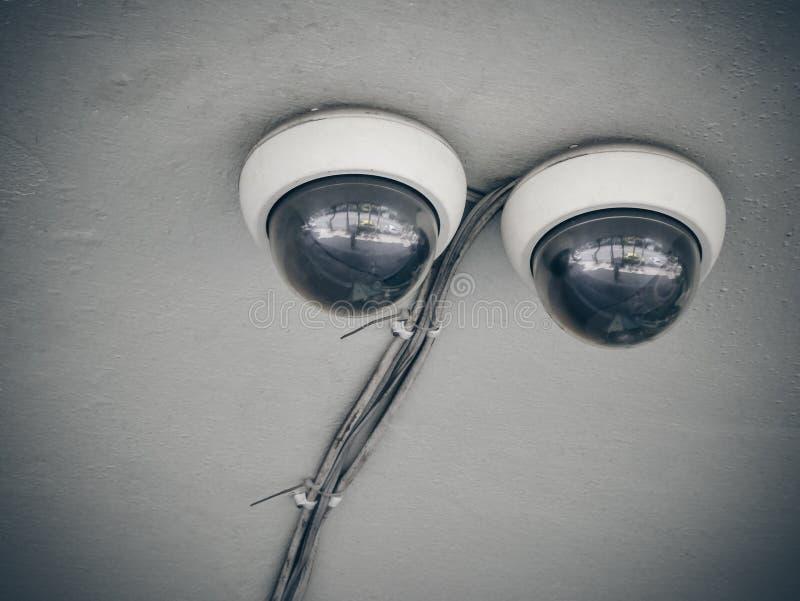 Dubbele kabeltelevisie-cameraveiligheid op oud concreet plafond stock afbeelding