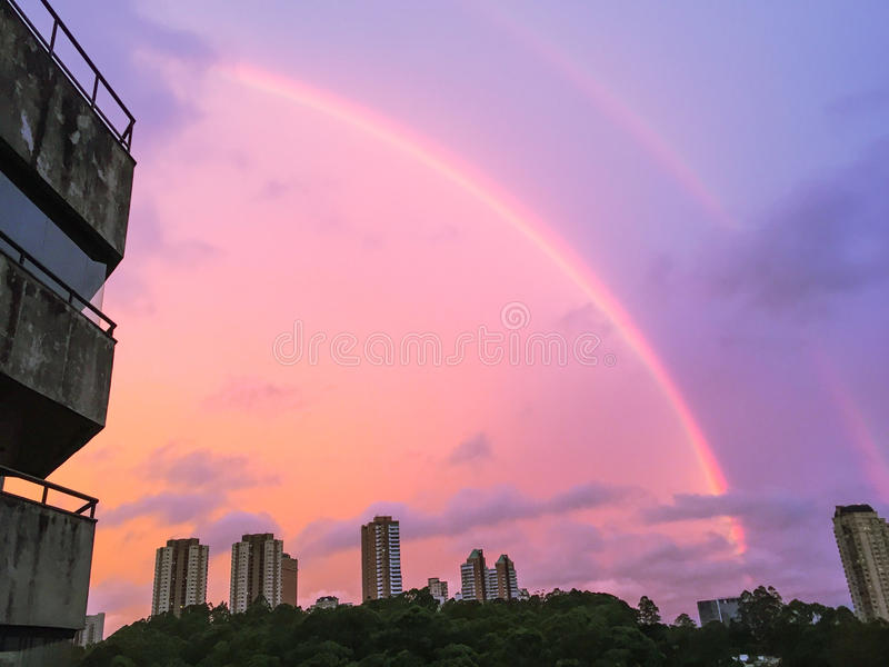 Dubbele regenboog en roze hemel over stadshorizon stock fotografie