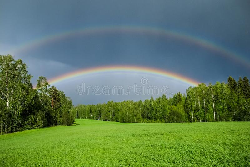 Dubbele regenboog over een groen gebied van de grasweide royalty-vrije stock foto's