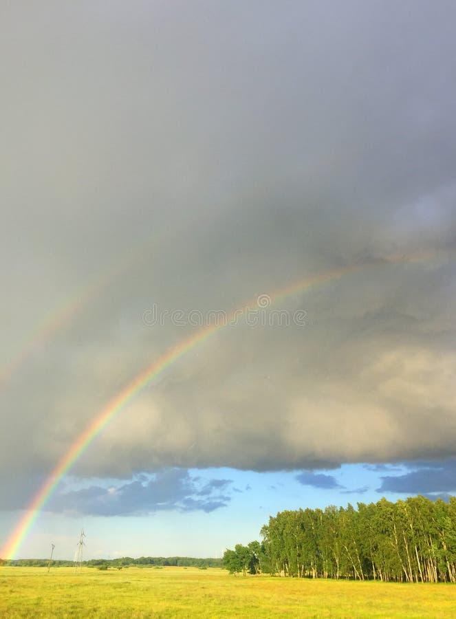 Dubbele regenboog over een weide royalty-vrije stock afbeelding