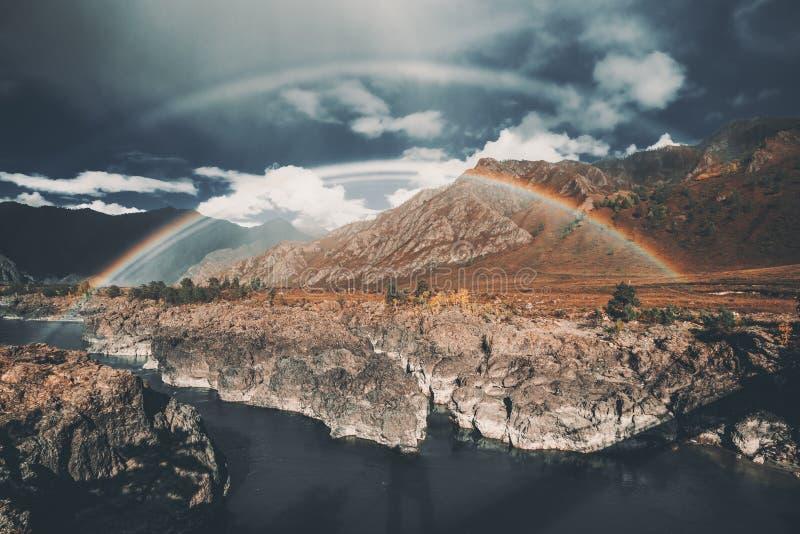 Dubbele regenboog over rivier, bergen stock afbeeldingen