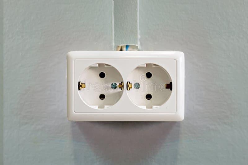Dubbele witte contactdoos op een grijze muur Close-up Front View Het aan de grond zetten en kabelkanaal royalty-vrije stock afbeeldingen