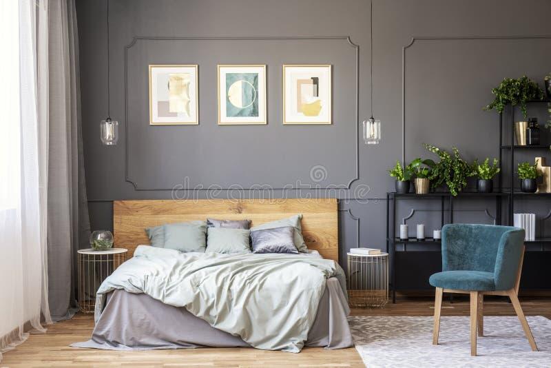 Dubbelsäng med grå sängkläder och trähuvudgavelanseende i da royaltyfri fotografi