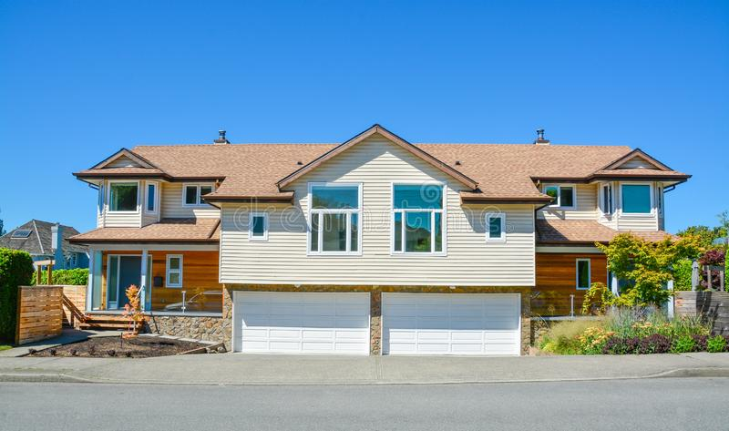 Dubbelsidigt hus för två familjer med breda garagedörrar längs vägen framtill fotografering för bildbyråer