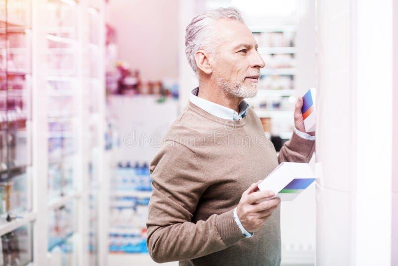 Dubbio del cliente che decide fra due scatole in una farmacia fotografie stock