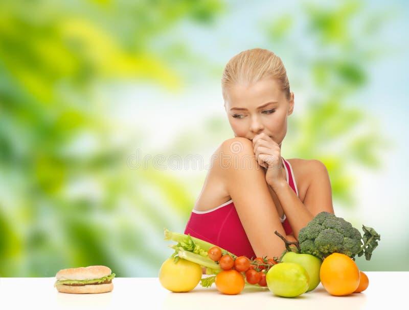 Dubbio della donna con i frutti che esaminano hamburger fotografia stock libera da diritti