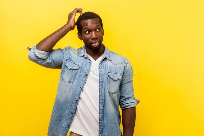 Dubbio, devo pensare Ritratto di un giovane incerto che pensa con il viso confuso studio interno isolato su sfondo giallo immagine stock