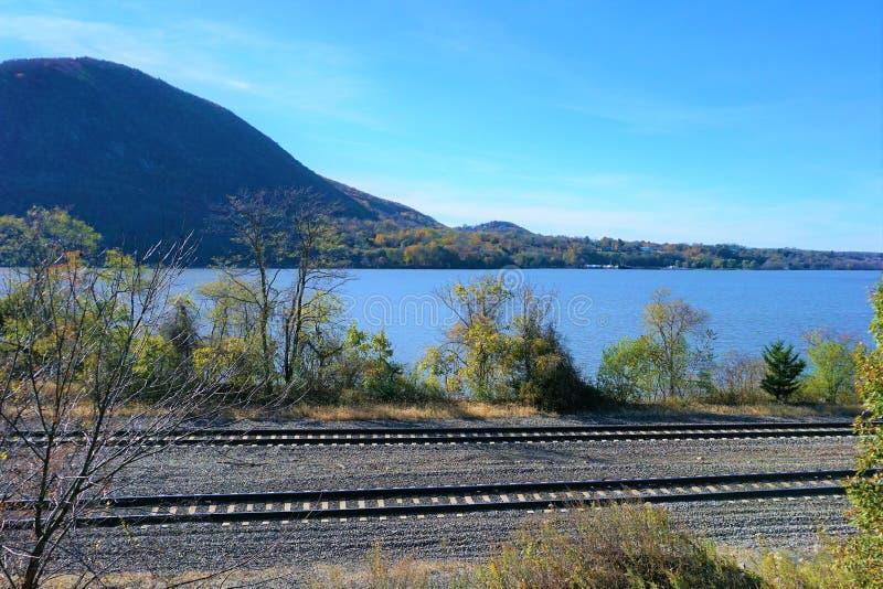 Dubbla spår bredvid Hudson River och berget arkivfoton